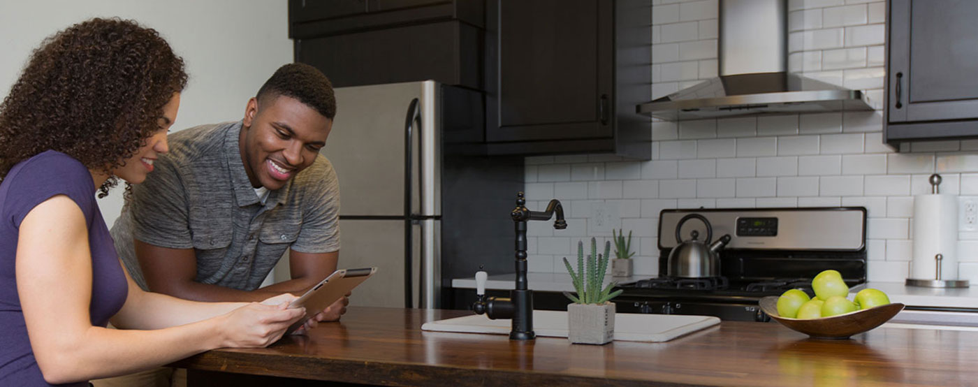 Man and woman looking at something on a kitchen island countertop