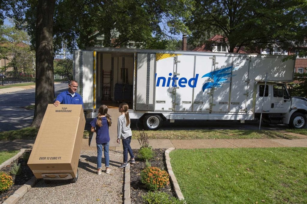 Movers moving stuff into a house